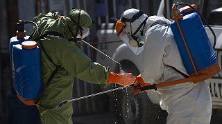 Des agents de plus grand hôpital de La Paz, en Bolivie, se désinfectant après être intervenus dans la morgue de l'établissement, le 5 août 2020