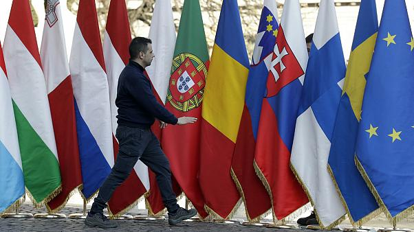 A man walks by flags of the EU member states