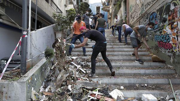 Varias personas limpian los destrozos tras la devastadora explosión en Beirut