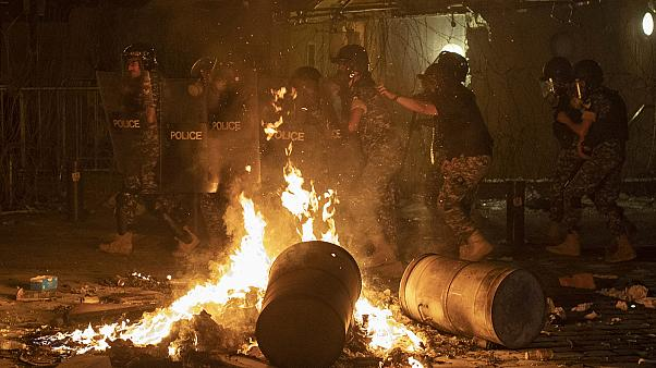 Riot police advance to push back anti-government protesters in Beirut on Thursday.