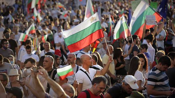 Protesters carry Bulgarian flags during mass protest in downtown Sofia, Bulgaria, on Wednesday, July 29, 2020.