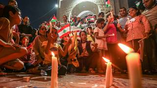 Palestinians attend a candle light vigil in Rafah in support of Lebanon