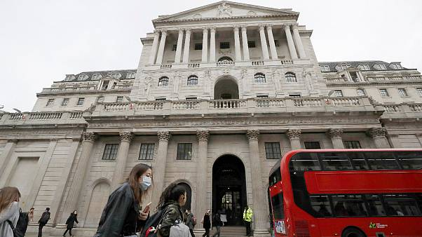 In this Wednesday, March 11, 2020 file photo, pedestrians wearing face masks pass the Bank of England in London.