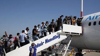 مهاجرون على متن طائرة متجهة إلى العراق في مطار الفثيريوس فينيزيلوس الدولي في أثينا