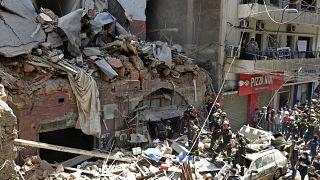 طاقما إنقاذ، أحدهما لبناني والآخر فرنسي أمام مبنى انهار جراء الانفجار بالقرب من مرفأ بيروت
