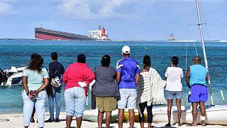 Des habitants de l'Île Maurice regardant le Wakashio d'où s'échappent des hydrocarbures, le 6 août 2020