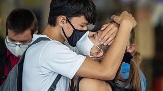 Una coppia, che indossa mascherine, si bacia all'aeroporto di Francoforte, Germania