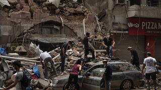 أشخاص يزيلون حطام منزل دمره انفجار الثلاثاء في ميناء بيروت، لبنان، وفرق الإنقاذ تبحث عن جثث بين الأنقاض