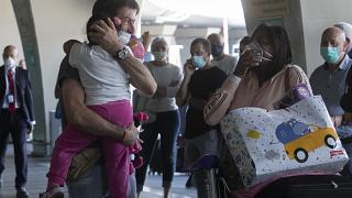 Sandro Manzato, from the Veneto region, hugs his daughter Yearline, 3, as she arrives with her mum Rubiela Perea, right, from Colombia, in Rome, June 3, 2020.