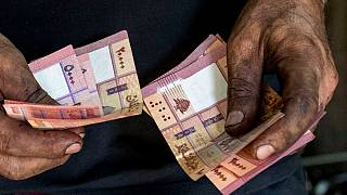 Un meccanico di biciclette conta i soldi nella sua officina, a Beirut, in Libano, nel maggio 2020