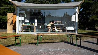 """An artist performs behind the glass wall of a container during the """"Please Don't Touch"""" performance in Litschau, Austria."""