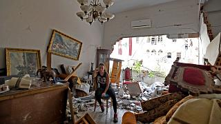 A woman sits among the rubble in her damaged house in the Lebanese capital Beirut on August 6, 2020, after a massive explosion shook the city