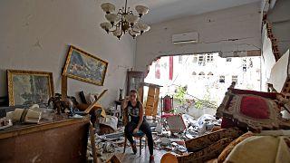 Une femme se tient assise au milieu de sa maison dévastée par l'explosion dans le port de Beyrouth, le 6 août 2020