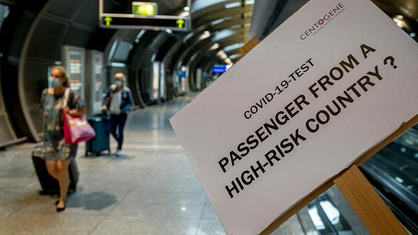 A sign helps passengers to find the COVID-19 test center at the airport in Frankfurt, Germany, Saturday, Aug. 8, 2020