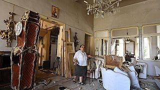 Egy bejrúti asszony mutatja a robbanásban romossá vált otthonát