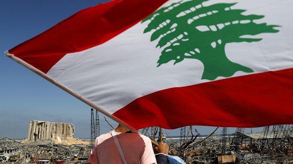 مردی با در دست داشتن پرچم لبنان به ویرانههای ناشی از ��نفجار بیروت مینگرد