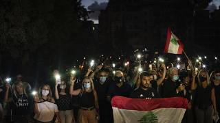 Demonstrators march holding candles and flashlights honoring the victims of the deadly explosion at Beirut port which devastated large parts of the capital, in Beirut, Lebanon