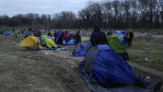 مهاجرون يحزمون أمتعتهم في مخيم مؤقت في كاليه ، شمال فرنسا