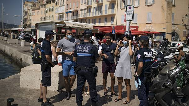 Police give masks to tourists walking along the Saint-Tropez port.