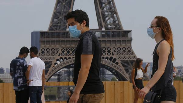 People wearing masks to prevent the spread of COVID-19 walk at Trocadero plaza near Eiffel Tower in Paris, Saturday, Aug 8, 2020.