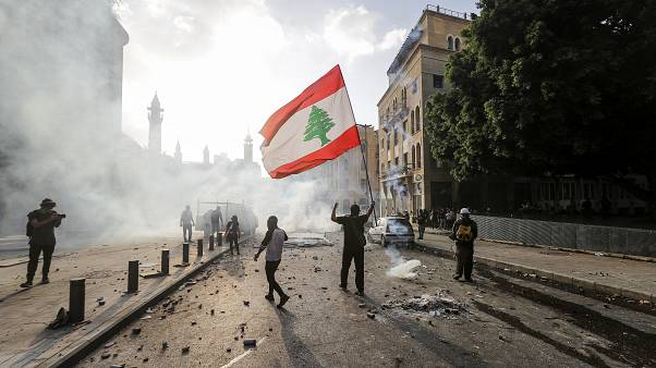 A Lebanese protester waves the national flag during clashes with security forces in downtown Beirut on August 8, 2020.