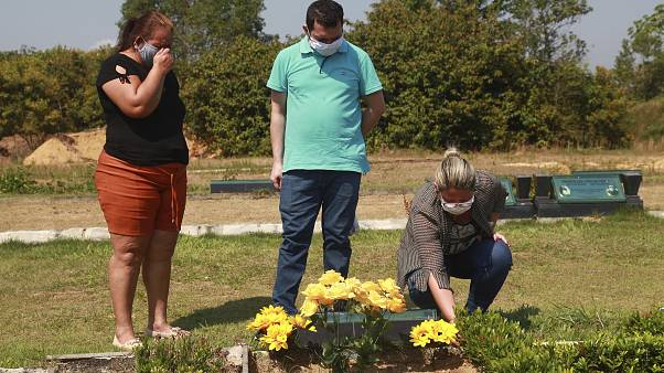 Sisters Valeria Melo da Silva, left, and Viviane, her husband Luigi do Nascimento visit the grave of their mother who died of COVID-19 at a cemetary in Brazil.