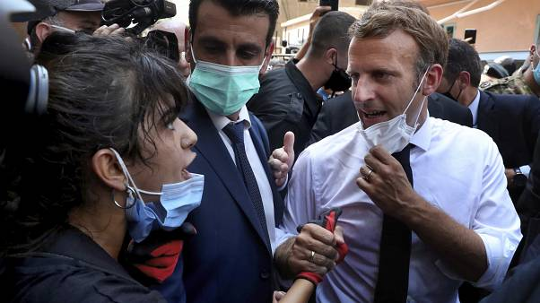 French President Emmanuel Macron, right, speaks with a woman as he visits the Gemayzeh neighborhood, which suffered extensive damage from the explosion in Beirut.