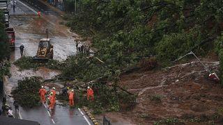 رجال الإطفاء يمهدون طريقًا بعد إنهيار أرضي ناجم عن هطول الأمطار