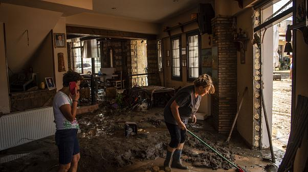 People try to move away water and mud from their shop, following a storm at the village of Politika, on Evia island, Greece.