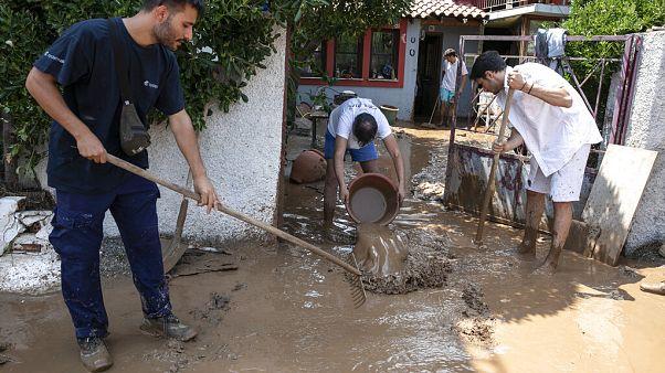 Un grupo de vecinos limpian los bajos de su casa en la isla de Eúbea (Grecia)