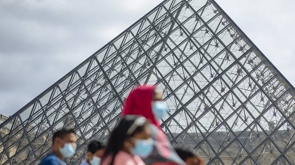 A family wearing face masks walk past the Louvre Museum in Paris on Saturday