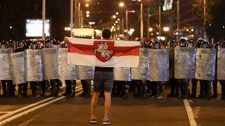 Un manifestant face aux policiers avec l'ancien drapeau du Bélarus, à Minsk, le 9 août 2020, Bélarus