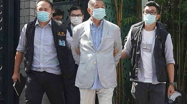 Hong Kong media tycoon Jimmy Lai, center, who founded local newspaper Apple Daily, is arrested by police officers at his home in Hong Kong, Monday, Aug. 10, 2020.