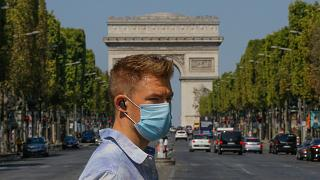 A man wearing a masks to prevent the spread of COVID-19 crosses the Champs Elysees avenue in Paris, Sunday, Aug 9, 2020.