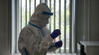 A Semmelweis Egyetem szakembere nyálkahártyamintát kezel a sziráki orvosi rendelőben 2020. május 8-án.