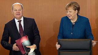German Chancellor Angela Merkel arrives besides Vice Chancellor and Finance Minister Olaf Scholz