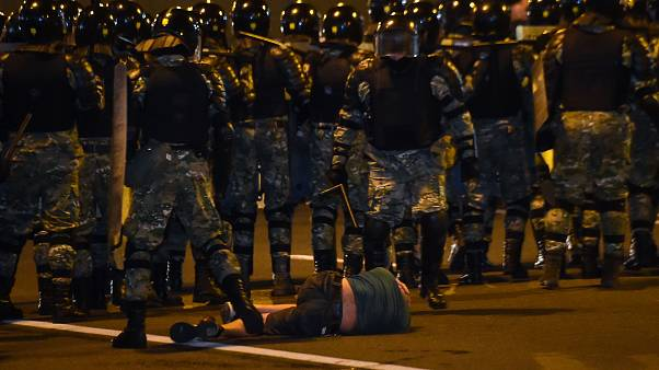 A man lies on the ground in front of riot police during a protest after polls closed in Belarus' presidential election, in Minsk on August 9, 2020.
