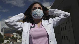 Dr. Maria Jose Casco adjusts her hair as she walks near her home in Quito, Ecuador, Wednesday, Aug. 5, 2020.