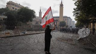 Egy nő libanoni zászlót lenget szemben a rendőrsorfallal