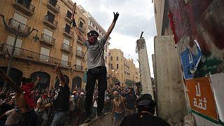 Tüntetők ünnepelnek Bejrútban, miután sikerült lebonatniuk egy betonakadályt, ami a parlamenthez vezető utat zárta le