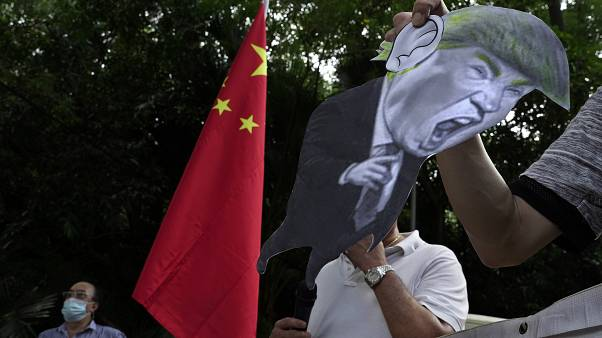 In this Aug. 8, 2020, file photo, pro-China supporters display a picture of US President Trump during a protest against US sanctions outside the US Consulate in Hong Kong.