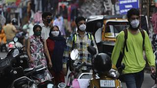 Indians wearing face masks as a precaution against the coronavirus walk at a market in Jammu, India, Monday, Aug 10, 2020.