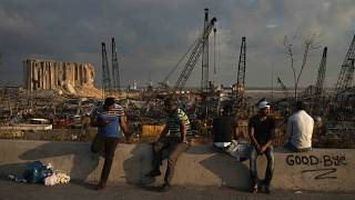 People sit near the site of last week's explosion that hit Beirut's port