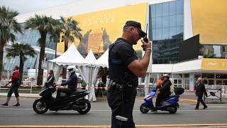 FILE - A police officer patrols in front of the entrance of the Festival Palace in Cannes, May 2016.