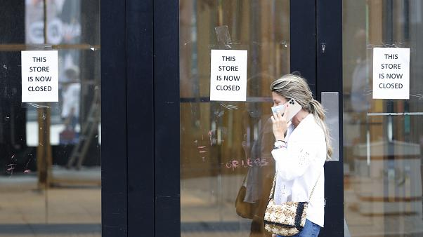 A woman walks by a closed store, in London, Thursday, July 16, 2020. Figures show UK employment suffered the biggest three-month decline since the 2009 recession.