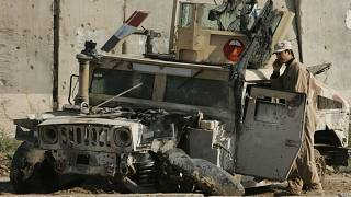 An Iraqi army soldier talks on his phone as he stands next to an army vehicle damaged in previous fighting, at an Iraqi army base in Sukor neighborhood