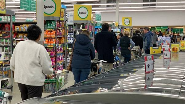 People queuing inside supermarket, waiting to checkout