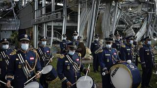 A scouts band performs in honor of the victims of the last week's explosion, the city, near the blast site in Beirut, Lebanon, Tuesday, Aug. 11, 2020.