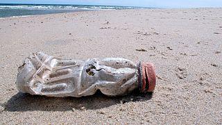 Una bottiglia di plastica su una spiaggia