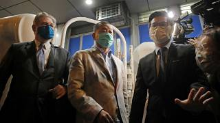Hong Kong media tycoon and newspaper founder Jimmy Lai, center, walks out from a police station after being bailed out in Hong Kong